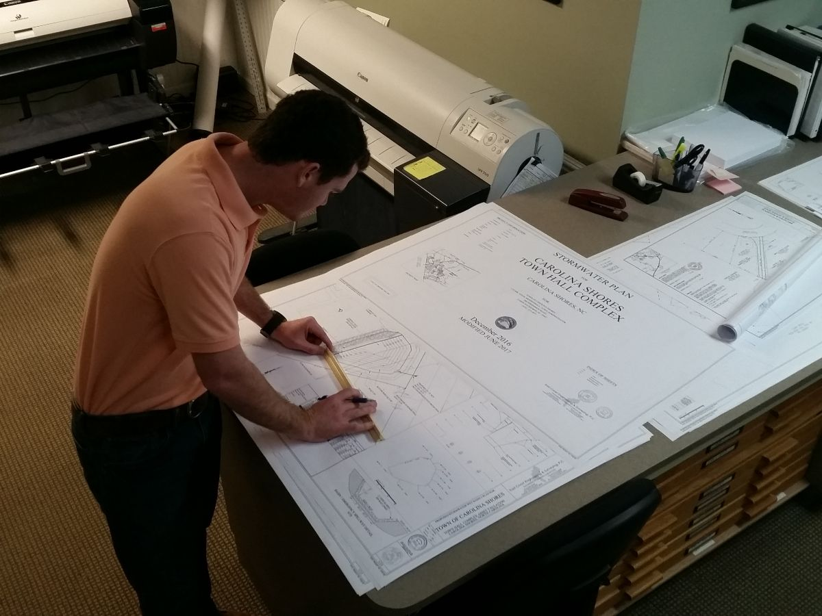 planning engineer working on plans and specs on drafting table